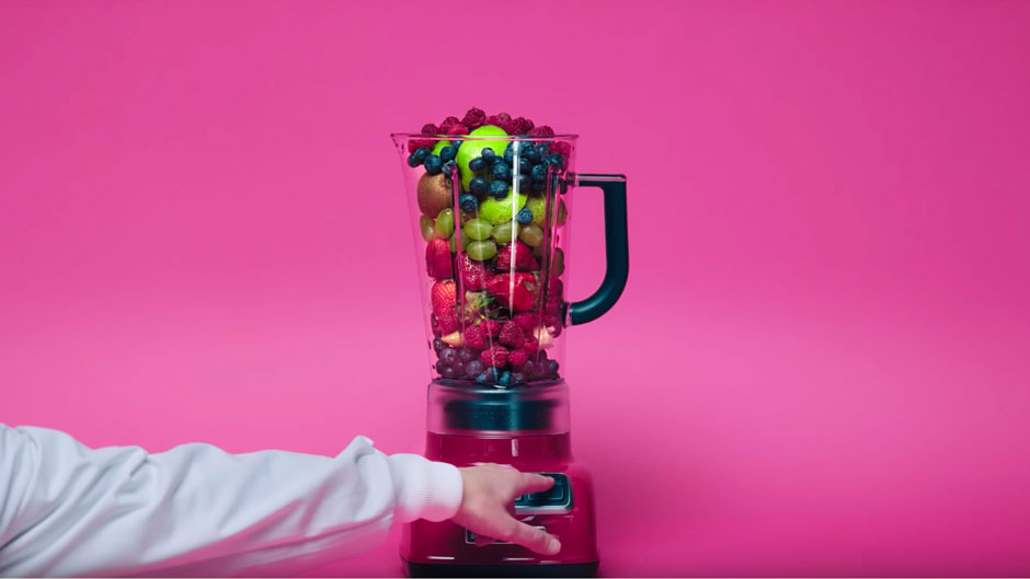 scientist blending fruit in a machine in a pink studio